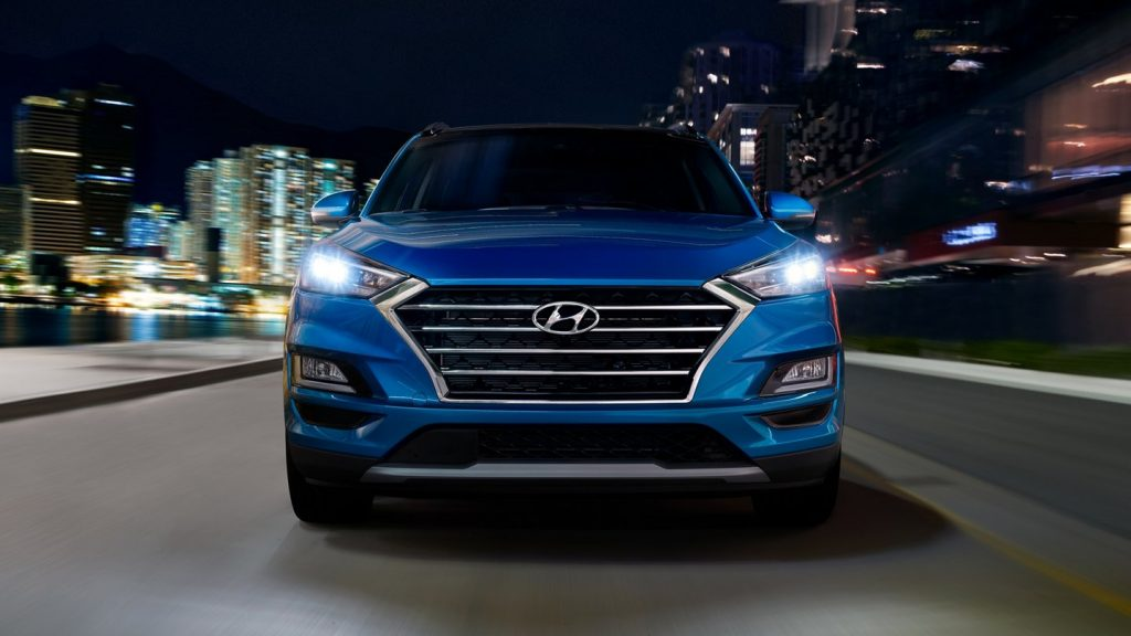 Front grille of a blue 2020 Tuscon driving through a city at night