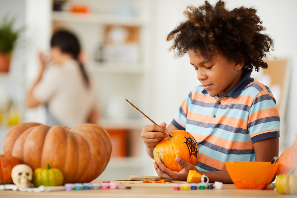Child painting a pumpkin in his kitchen