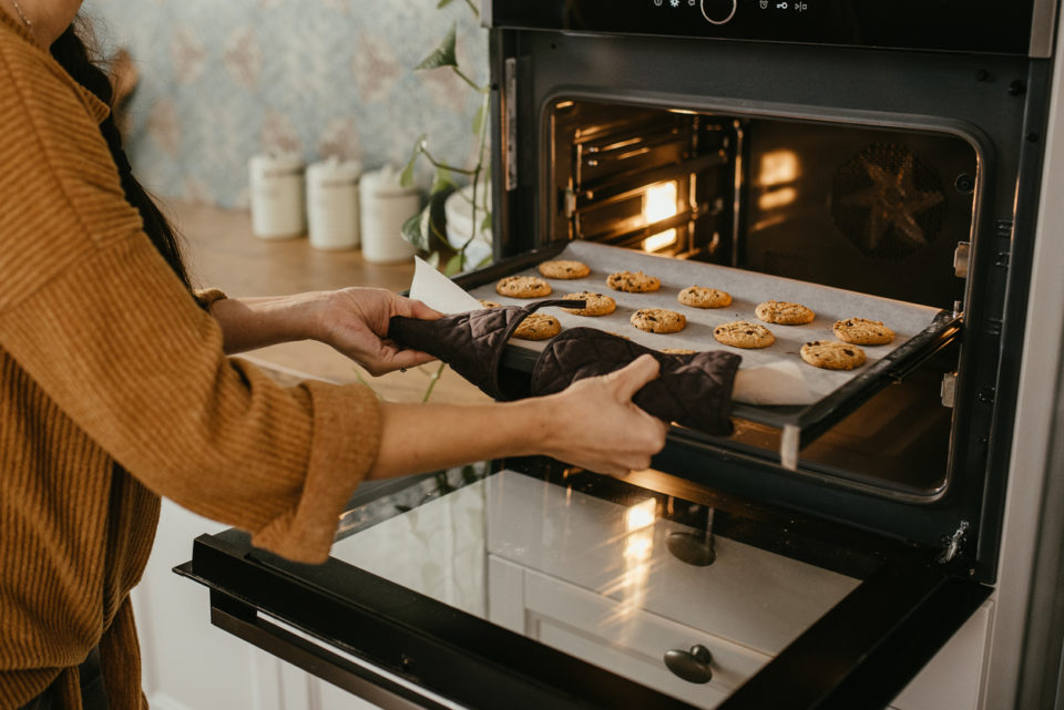 Putting tray of cookies into oven