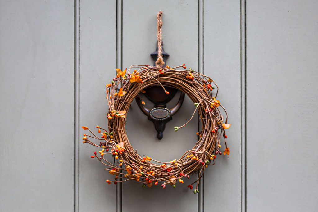 A decorative wreath with berries, hanging on the outside of a door