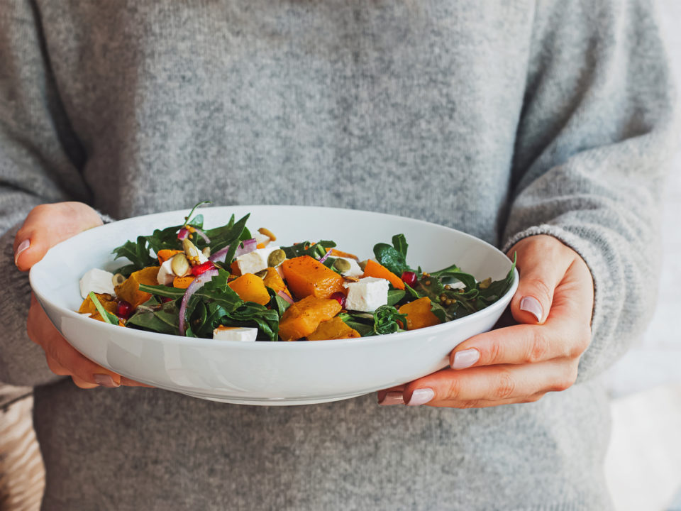 Woman holding a bowl of salad with pumpkin, arugula, feta cheese and pomegranate seeds.