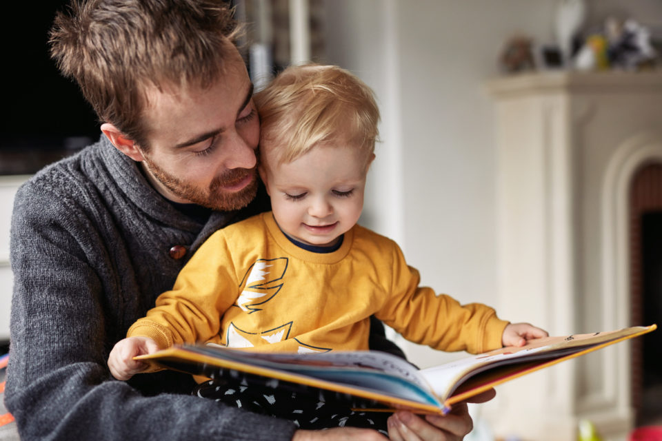 Boy reading a book while sitting with his father at home
