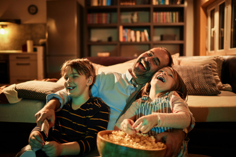Close up of a father watching television with his kids