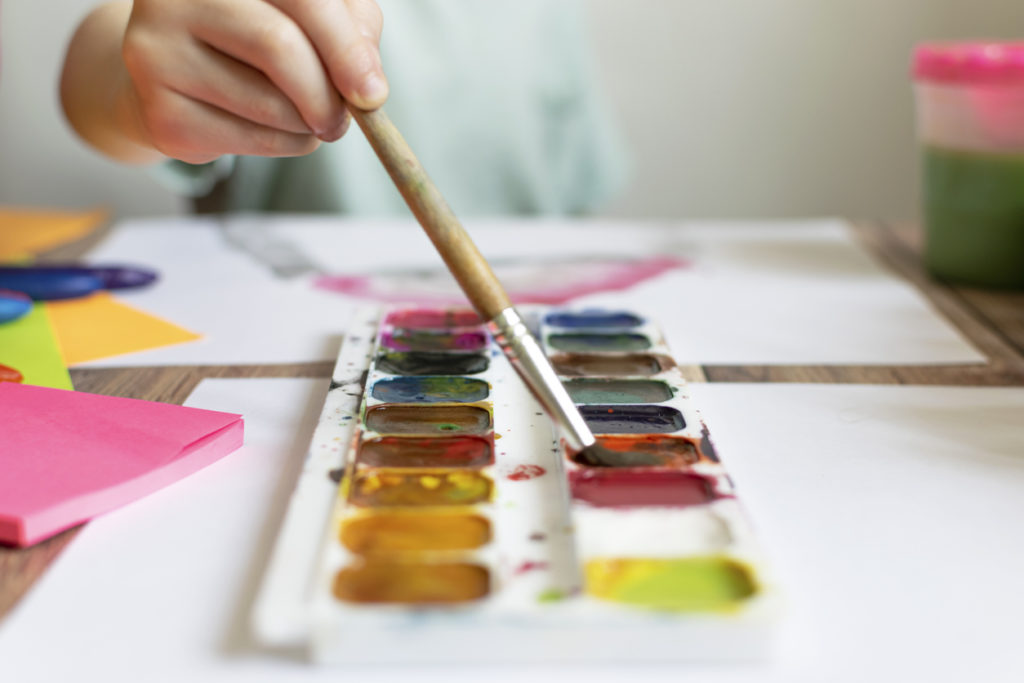 Child painting with a brush and watercolor paint