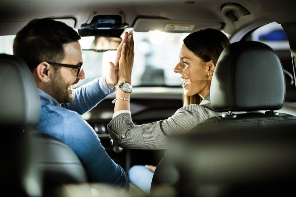 Happy couple high fiving after buying a car