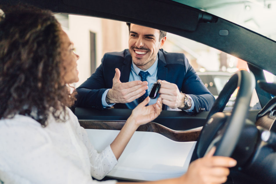 Smiling woman in the showroom enjoying luxury car